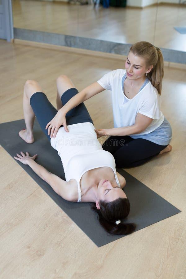 Persoonlijke trainer, pilates Fysiotherapeut die Kaukasische vrouw in haar training bij geschiktheidsstudio, geselecteerde nadruk stock foto