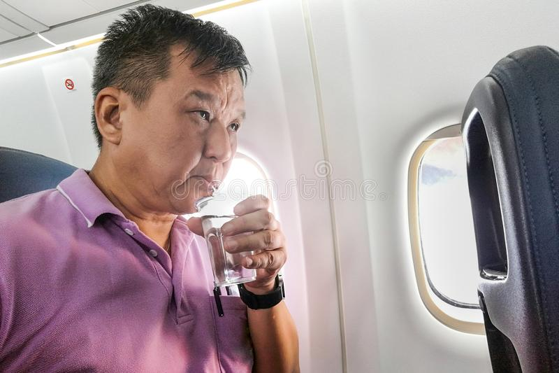 Persoons drinkwater in vliegtuigvlucht op lange afstand aan hydraat royalty-vrije stock fotografie