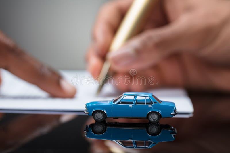 Persoons` s Hand die de Overeenkomstencontract ondertekenen van de Autolening stock afbeeldingen