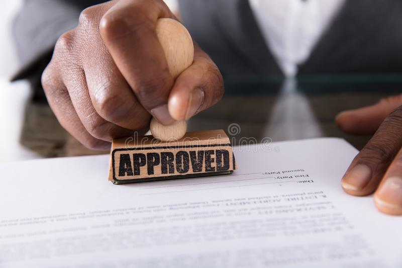 Persoons` s Hand het Stempelen op Goedgekeurde Contractvorm stock afbeeldingen
