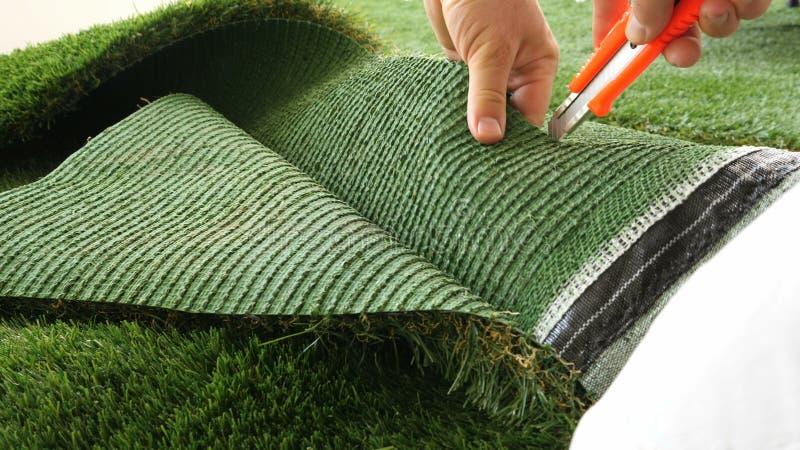 Persoons scherp blad van kunstmatig gras stock afbeelding