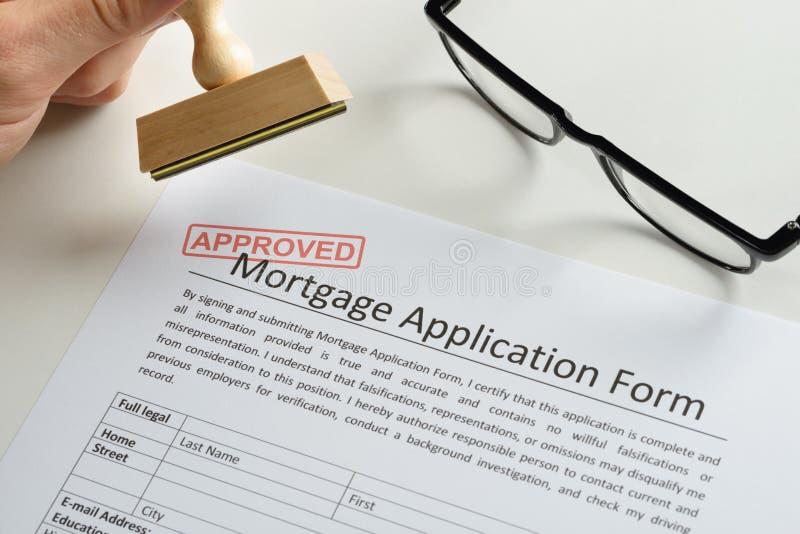 Persoonshand met zegel en goedgekeurd teken op hypotheektoepassing royalty-vrije stock foto