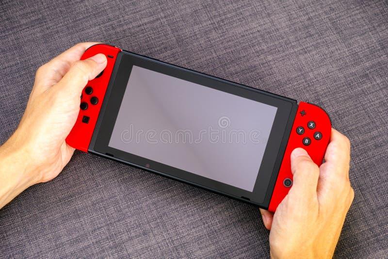 Persoonshanden die Nintendo-de console van het Schakelaarvideospelletje houden royalty-vrije stock afbeeldingen