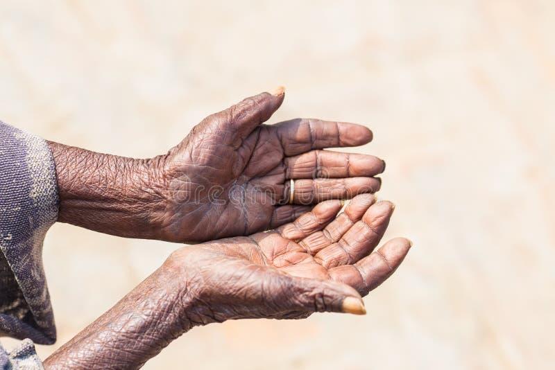 Persoonshanden die voor voedsel of hulp bedelen stock foto's