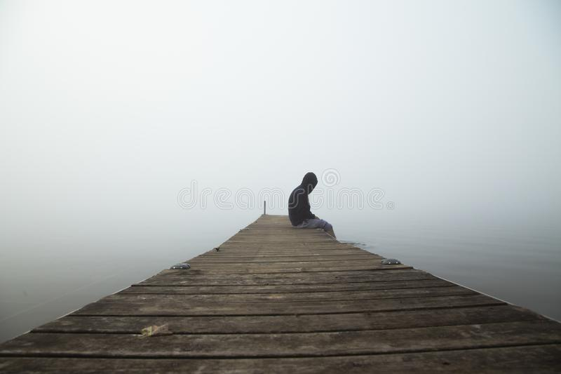 Persoonszitting op dok vroege ochtend met mist in de hemel stock afbeelding