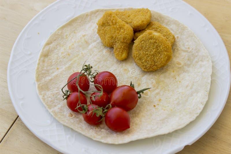 Perspectief van kippengoudklompjes en kleine rode verse tomaten op de brede witte plaat als ontbijt op centrum wordt geschoten da stock foto