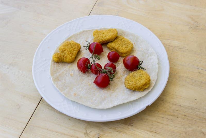 Perspectief van kippengoudklompjes en kleine rode verse tomaten op de brede witte plaat als ontbijt met dun brood op centrum word stock fotografie