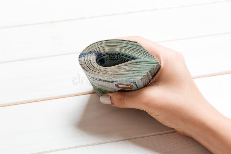 Perspectief voor vrouwelijke hand die een pak geld vasthoudt op houten achtergrond Honderd dollar Bedrijfsconcept liefdadigheid e royalty-vrije stock fotografie