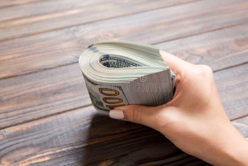 Perspectief voor vrouwelijke hand die een pak geld vasthoudt op houten achtergrond Honderd dollar Bedrijfsconcept liefdadigheid e stock foto's