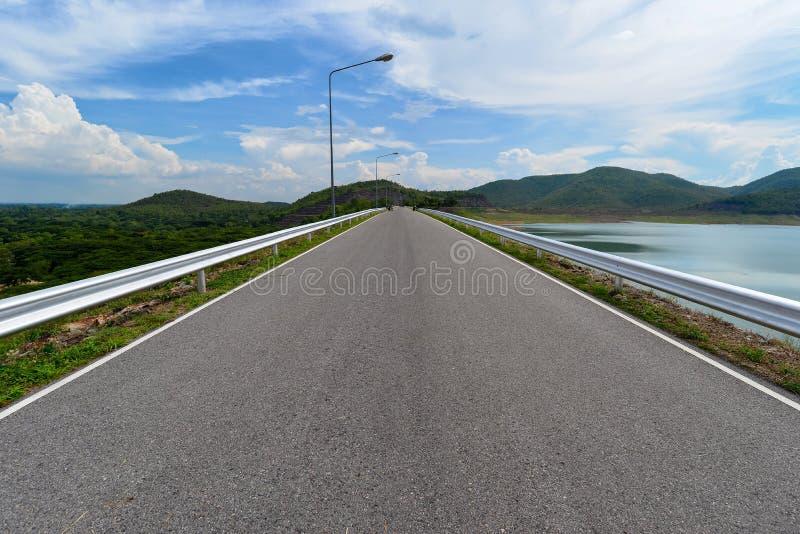 Perspectiefmening die van weg op de dam met mening van boom in bos en water kruisen resevoir stock foto's