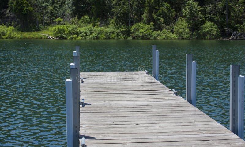 Perspectiefmening van hout en metaaldok op een meer. stock foto's