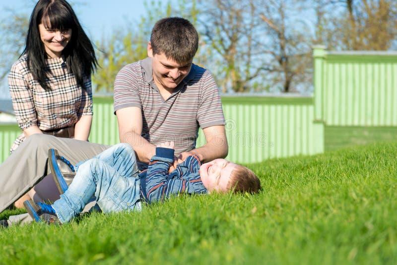 Perspectiva única de dois pais loving que encontram-se na grama com seu bebê foto de stock royalty free