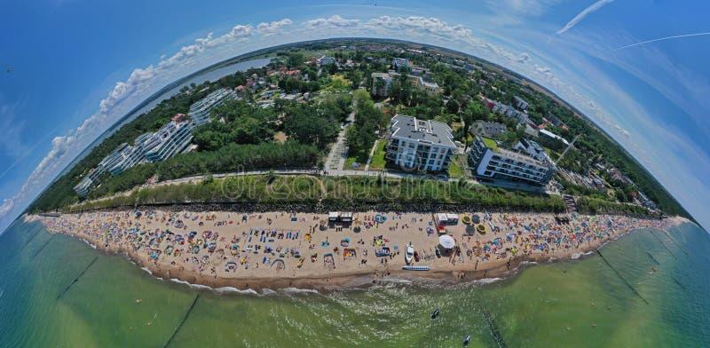 Perspectiva aérea del abejón y opinión panorámica sobre la playa soleada con los persona que toma el sol con los guarda-brisas y  fotografía de archivo libre de regalías