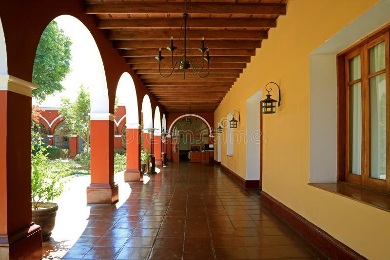 Perspectiva de disminución del pasillo colorido del edificio peruano del vintage en la ciudad del oasis del desierto de Huacachin imagenes de archivo