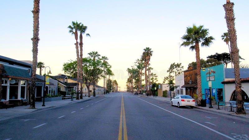 Perspectiva de la calle con las palmeras en salida del sol de la mañana foto de archivo libre de regalías