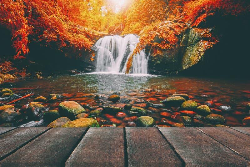 Perspectiva de madera del piso y cascada natural de la montaña fotografía de archivo libre de regalías