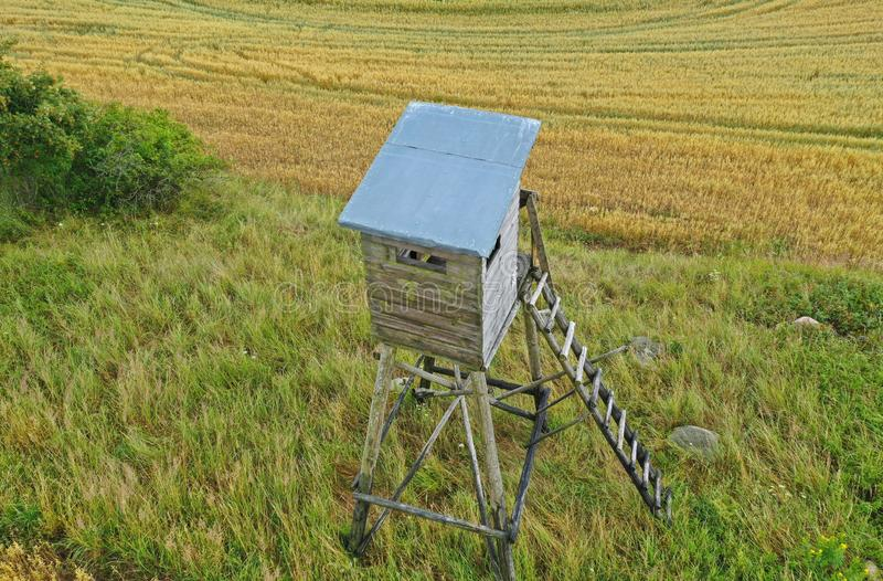 Perspective aerial drone view on wooden hunting tower in fields and meadows surroundings stock image