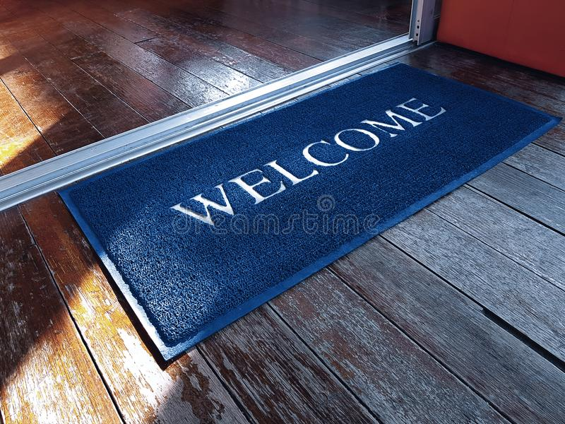 Blue Doormat with Welcome Text in Front of Shop royalty free stock photos