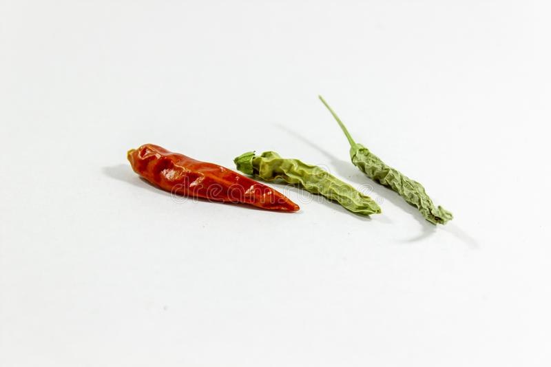Perspective close-up shoot of dried red and green colored peppers on white background stock photo