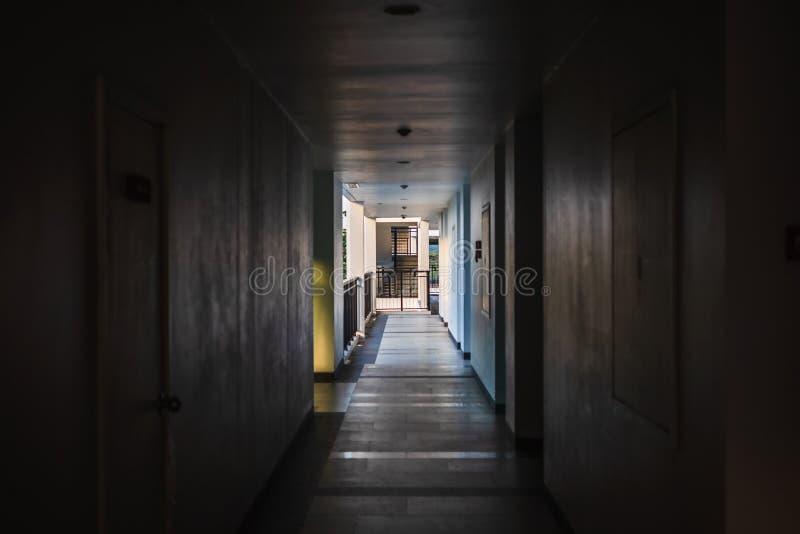 Perspective de couloir vide dans l'immeuble avec les portes et et la sortie de secours et la lumi?re ? la fin de la mani?re photos libres de droits