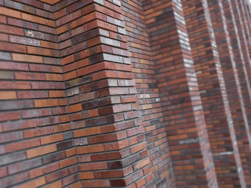 Perspective diagonal view on abstract brown red brick wall with columns with blured background. Architecture element brown brick w stock photography