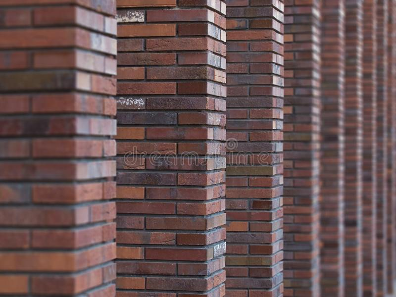 Perspective diagonal view on abstract brown red brick wall with columns with blured background. Architecture element brown brick w stock images