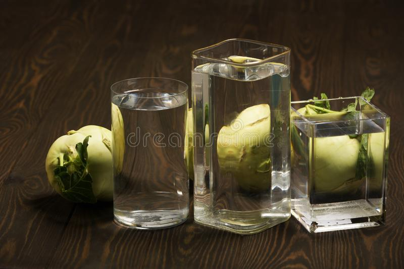 Foods distorted through liquid and glass on dark wooden background. Perspective, fractured and skewed images of common foods as seen through vessels filled with stock photography