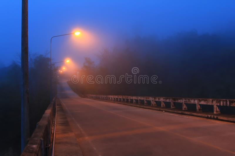 Perspective landscape concrete road bridge with lamppost in nigh royalty free stock photos