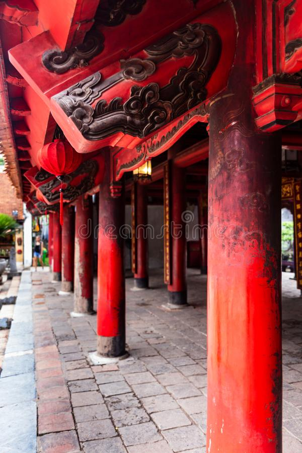 Perspective of red wooden roof beams and pillars with black engravings in the Temple of Literature Quoc Tu Giam, Hanoi, Vietnam. Perspective of red wooden roof stock image