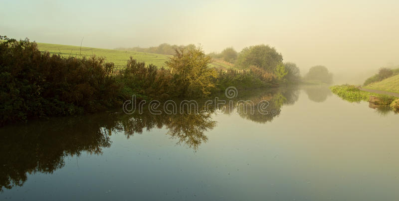 Perspective. Reflections on the water of a canal on a misty morning, which vanish into a misty distance royalty free stock photo