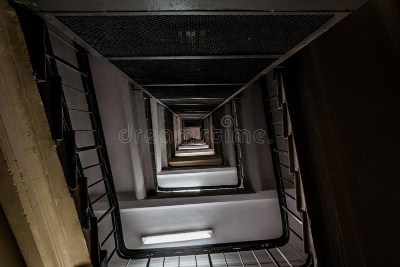 perspective of a staircase interior. Old vintage squared spiral multi-flight stairs in tenement house stock images