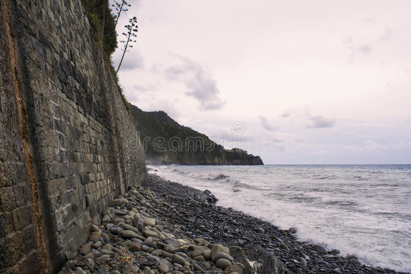 Perspective of a stone wall on a rocky beach, a windy day. Perspective of a stone wall on a rocky beach. Windy weather with dramatic clouds in the sky. Waves stock photo