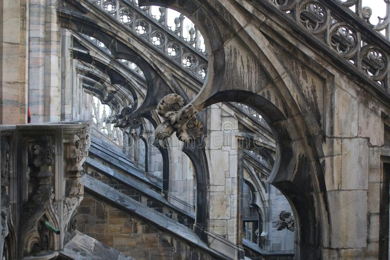 The perspective and strict symmetry of the flying buttresses of the Milan Cathedral stock image