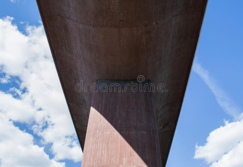 Perspective from under a huge, concrete bridge against summer sky stock photo