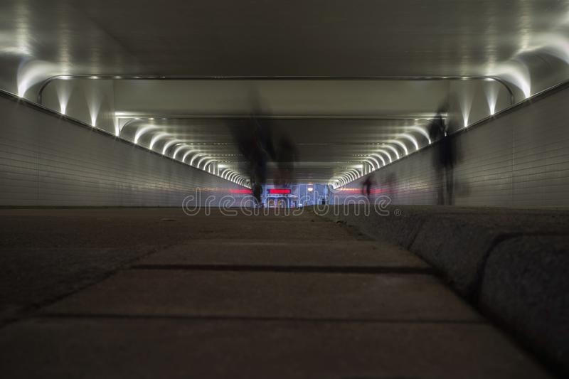 Perspective of an underground tunnel with silhouettes of people walking by.  royalty free stock images