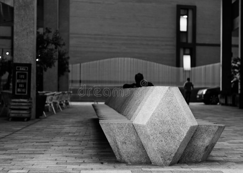 Perspective view of concrete bench with a silhouette of a man. Sitting. Chairs, fence, and building exterior wall in the background. Black and white photograph stock photo