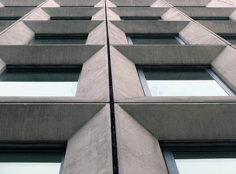 Perspective view of geometric angular concrete windows on the facade of a modernist 1960s brutalist style building stock images