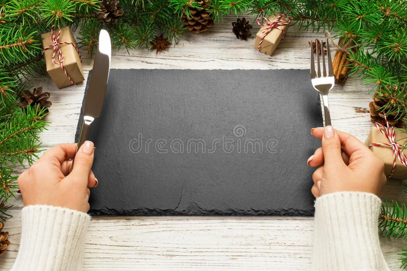 Perspective view girl holds fork and knife in hand and is ready to eat. Empty black slate rectangular plate on wooden christmas. Background. holiday dinner dish royalty free stock image