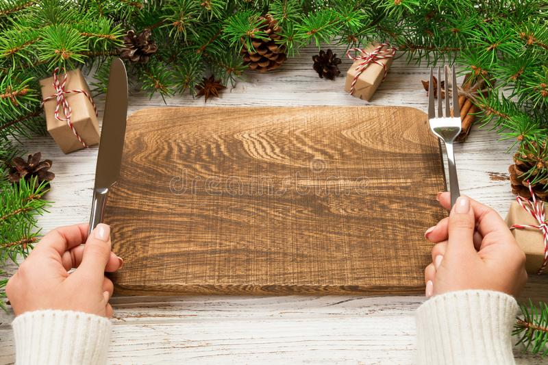 Perspective view girl holds fork and knife in hand and is ready to eat. Empty wood rectangular plate on wooden christmas. Background. holiday dinner dish stock photos