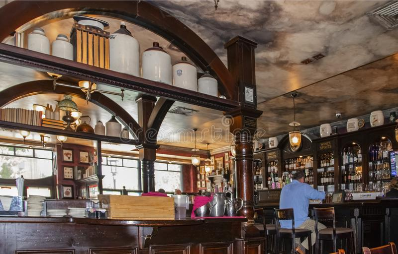 Perspective view inside of Kilkenneys Pub with faux marble ceiling and old Irish bar all along one wall stock images
