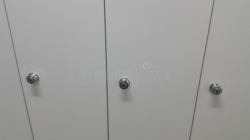 Perspective view of lockers or cupboards in a row with white doors royalty free stock images