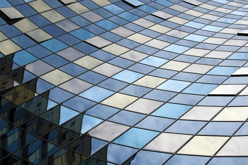 Perspective view of the modern glass building facade with reflections on the windows. Architectural pattern. Perspective view of the modern building facade with royalty free stock image