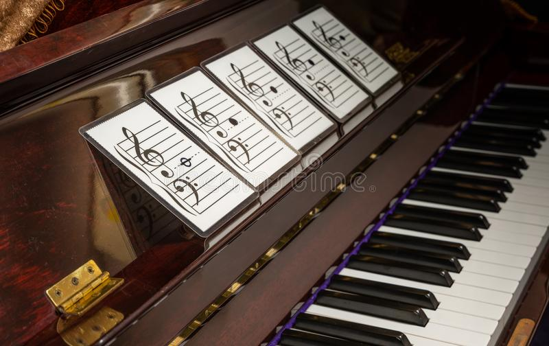 Music note on flash cards. Perspective view of music note on flash cards. Flash cards of music note on old piano royalty free stock photo