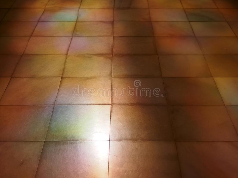 Perspective view of an old brown stone tiled floor with coloured light and sunlight reflections on the surface. A perspective view of an old brown stone tiled stock images