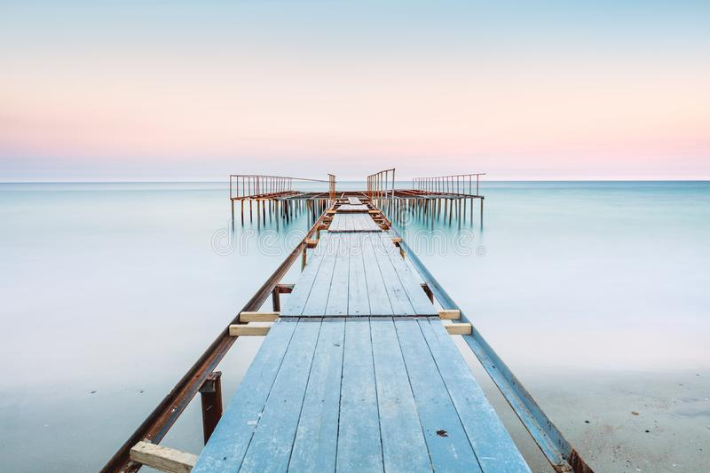 Long esposure view of a old jetty in a calm sea with gentle sky, soft colors. Perspective view of a old pier in a completely calm sea with gentle sky and clouds royalty free stock photos
