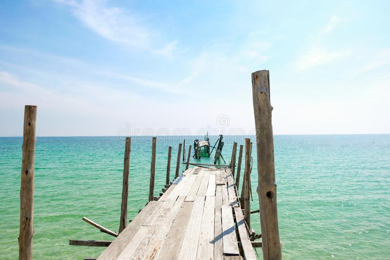 Perspective view of Old wooden bridge extending into the sea. stock images