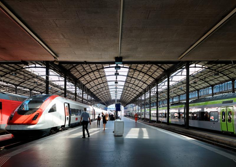Perspective view of a platform in Lucerne Central Railway Station with sunlight cast on trains parking by the platform stock photos