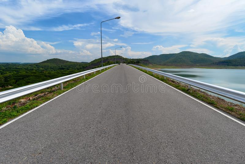 Perspective view of road crossing on the dam with view of tree in forest and water resevoir stock photos