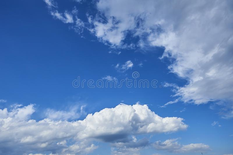 Perspective view of romantic navy blue sky with white grey clouds. High resolution artistic skyline background image stock image