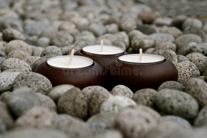 Perspective view of candles amongst pebbles stock photo